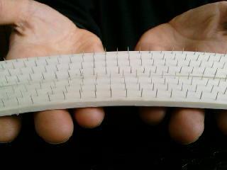 Proužek ohebné bílé gumy, do kterého jsou zapíchány jehly
